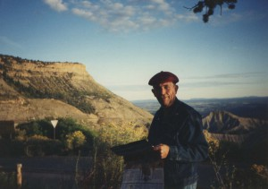 The author's father looking at a guide, with a big sky and plateau in the background