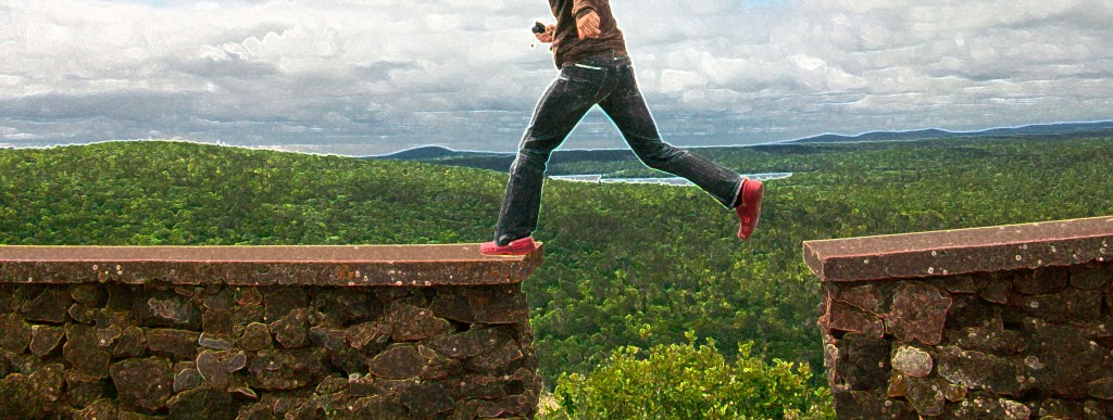 A person leaps from one stone wall to another, with greenery unfolding in the background